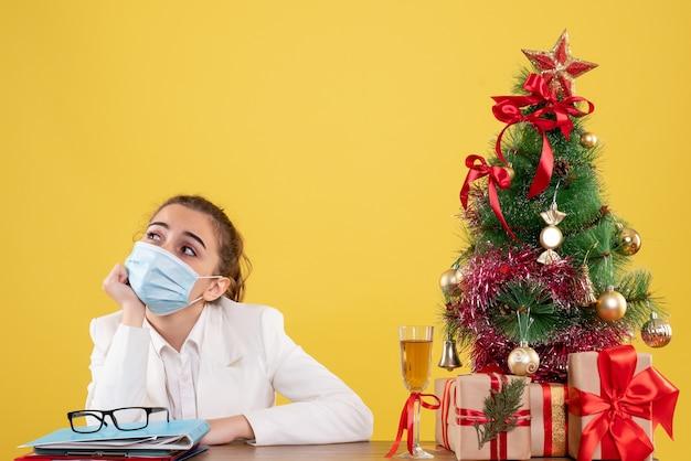 Vue de face femme médecin assis dans un masque stérile a souligné sur fond jaune avec arbre de noël et coffrets cadeaux