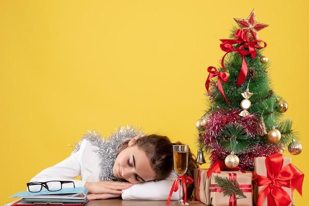 Vue de face femme médecin assis derrière sa table dormant sur fond jaune avec arbre de noël et coffrets cadeaux