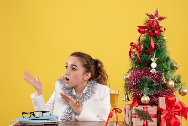Vue de face femme médecin assis derrière sa table sur un fond jaune avec arbre de noël et coffrets cadeaux