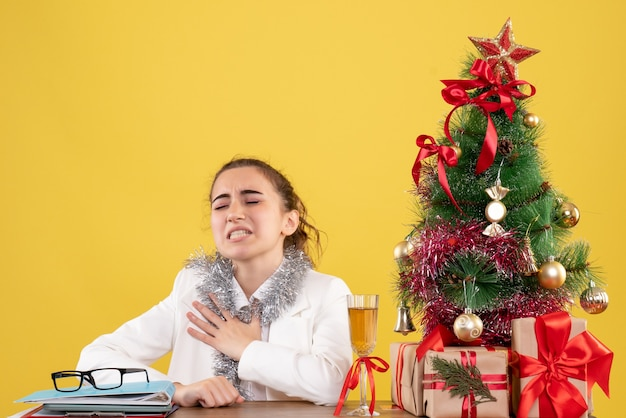 Vue de face femme médecin assis derrière sa table sur fond jaune vacances noël nouvel an émotion infirmière