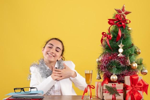 Vue de face femme médecin assis derrière sa table ravie sur fond jaune avec arbre de noël et coffrets cadeaux