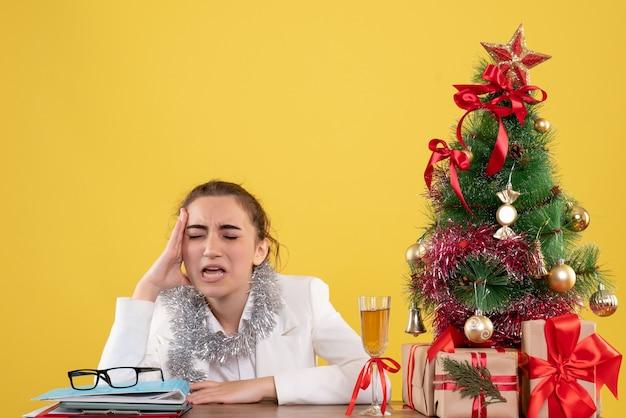 Vue de face femme médecin assis derrière sa table se sentant triste sur fond jaune avec arbre de noël et coffrets cadeaux