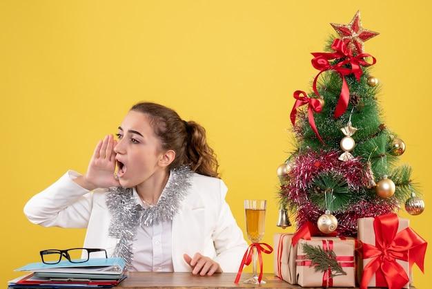 Vue de face femme médecin assis derrière la table avec des cadeaux de noël et arbre appelant sur fond jaune