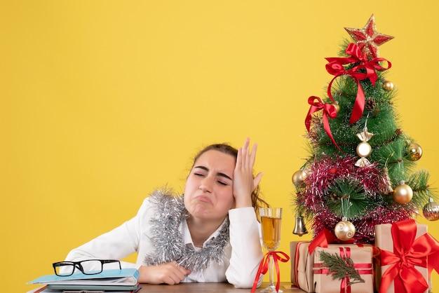 Vue de face femme médecin assis derrière la table avec des cadeaux de noël et arbre triste sur fond jaune