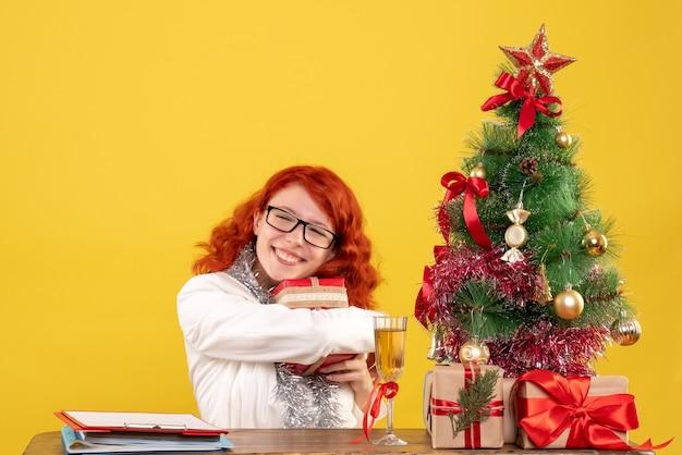 Vue de face femme médecin assis derrière la table avec des cadeaux de noël sur un bureau jaune avec arbre de noël et coffrets cadeaux