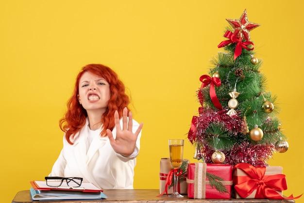 Vue de face femme médecin assis derrière la table avec des cadeaux de noël sur un bureau jaune