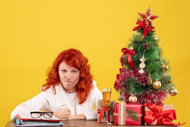 Vue de face femme médecin assis derrière la table avec des cadeaux de noël sur fond jaune