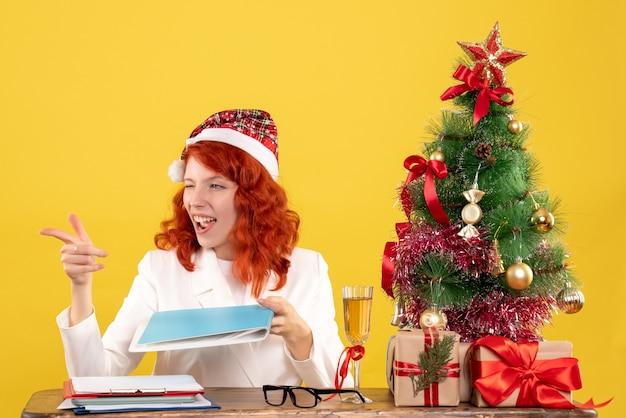 Vue de face femme médecin assis derrière la table avec des documents dans ses mains sur un bureau jaune avec arbre de noël et coffrets cadeaux
