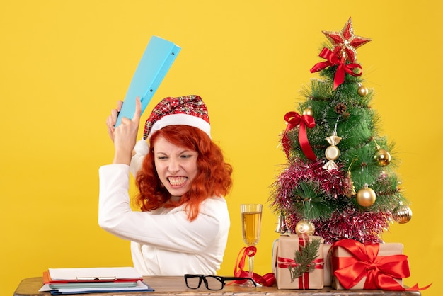 Vue de face femme médecin assis derrière la table avec des documents dans ses mains en colère sur fond jaune avec arbre de noël et coffrets cadeaux