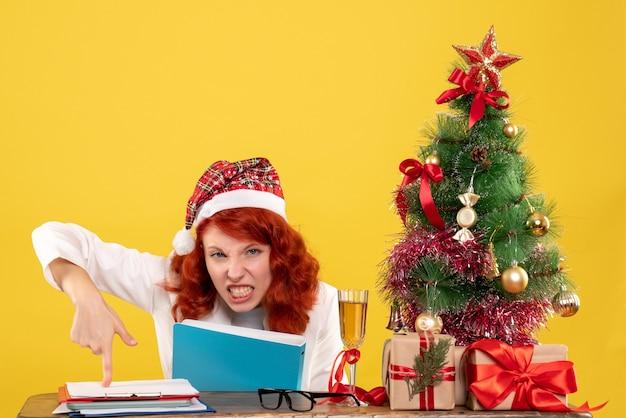 Vue de face femme médecin assis derrière la table avec des documents dans ses mains sur fond jaune avec arbre de noël et coffrets cadeaux