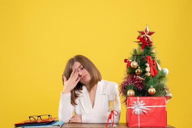 Vue de face femme médecin assis devant sa table sur un bureau jaune avec arbre de noël et coffrets cadeaux