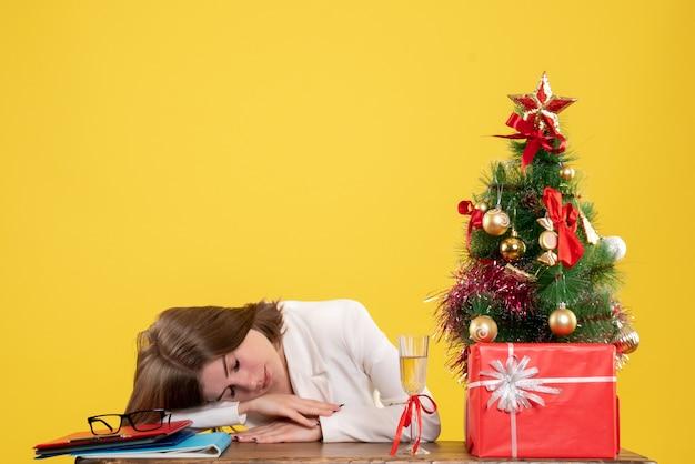 Vue de face femme médecin assis devant sa table dormant sur fond jaune avec arbre de noël et coffrets cadeaux