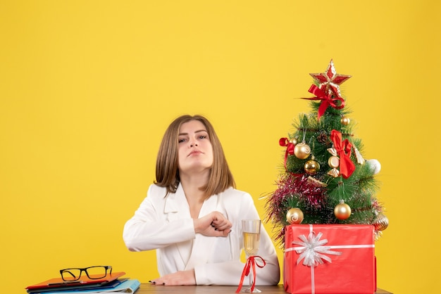 Vue de face femme médecin assis devant sa table sur fond jaune avec arbre de noël et coffrets cadeaux