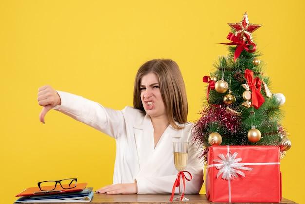 Vue de face femme médecin assis devant sa table mécontent sur fond jaune avec arbre de noël et coffrets cadeaux