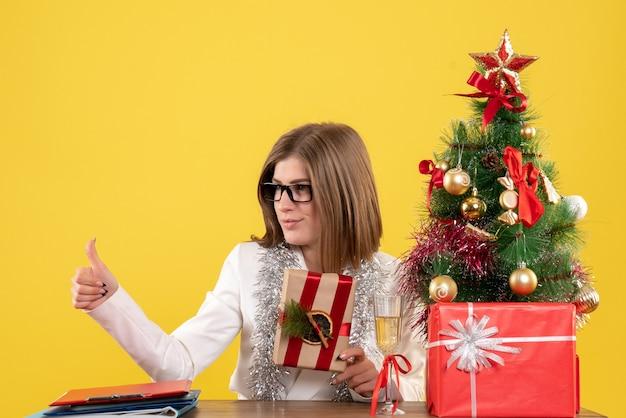 Vue de face femme médecin assis devant sa table tenant présent sur fond jaune avec arbre de noël et coffrets cadeaux