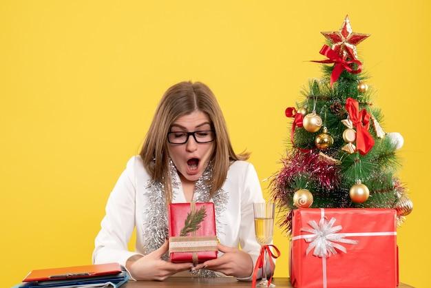 Vue de face femme médecin assis devant la table avec des cadeaux et arbre sur fond jaune avec arbre de noël et coffrets cadeaux