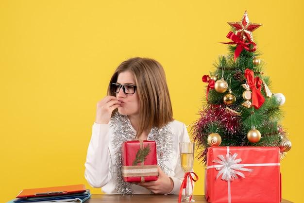Vue de face femme médecin assis en face de la table avec des cadeaux et arbre sur un bureau jaune