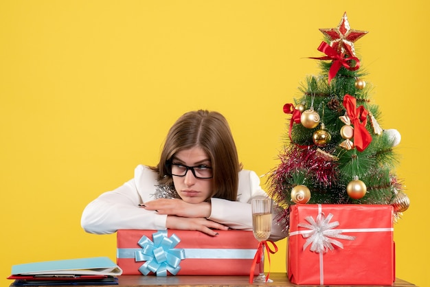 Vue de face femme médecin assis en face de la table avec des cadeaux et arbre sur jaune avec arbre de noël et coffrets cadeaux