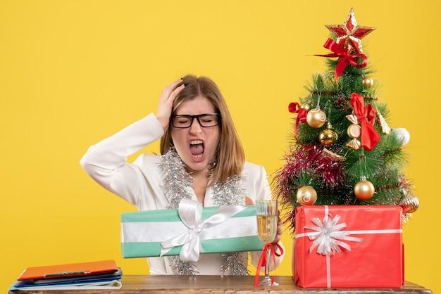 Vue de face femme médecin assis en face de la table avec des cadeaux et arbre de noël sur fond jaune
