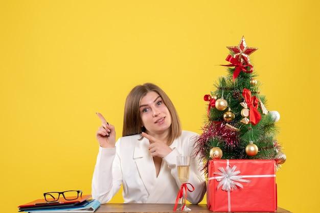 Vue de face femme médecin assis en face de table avec des cadeaux de noël et arbre sur fond jaune