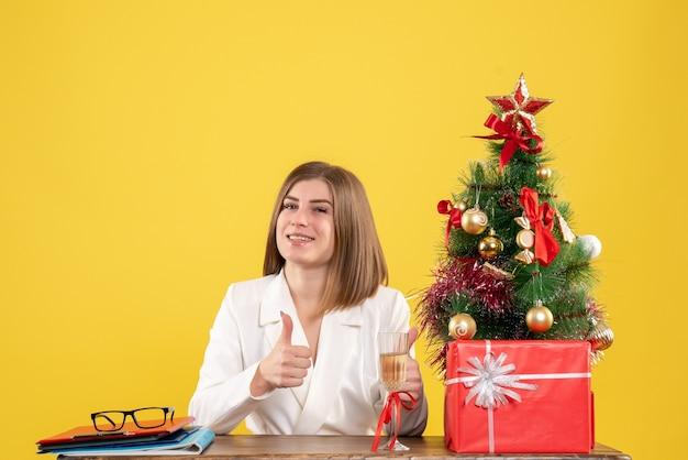 Vue de face femme médecin assis en face de table avec des cadeaux de noël et arbre souriant sur fond jaune