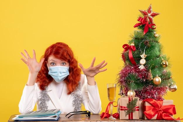 Vue de face femme médecin autour de l'arbre de noël et présente assis dans un masque stérile