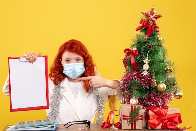 Vue de face femme médecin autour de l'arbre de noël et présente assis dans un masque