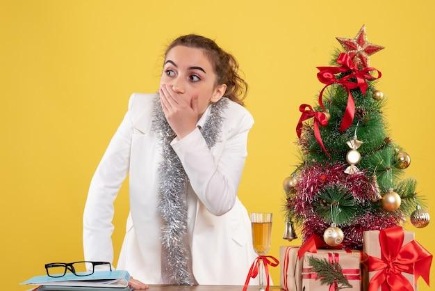 Vue de face femme médecin autour des cadeaux de noël et arbre au visage choqué