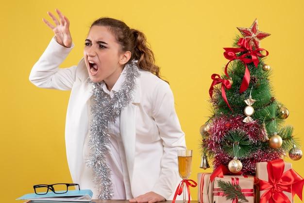 Vue de face femme médecin autour des cadeaux de noël et arbre en colère