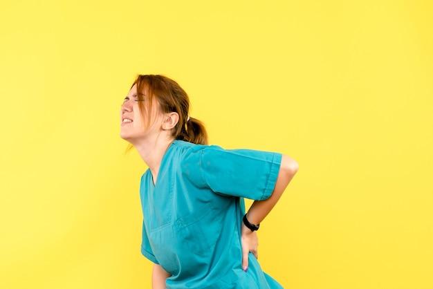 Vue de face femme médecin ayant mal au dos sur l'espace jaune