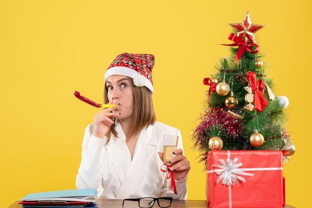Vue De Face Femme Médecin Célébrant Noël Avec Champagne Photo gratuit
