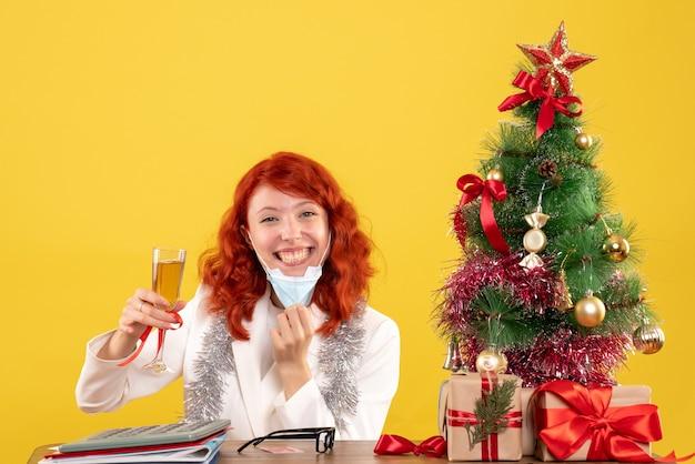 Vue de face femme médecin célébrant noël avec verre de champagne