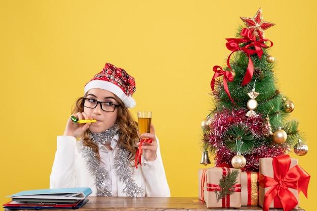Vue De Face Femme Médecin Célébrant Noël Avec Verre De Champagne Photo gratuit