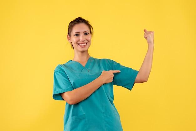 Vue de face femme médecin en chemise médicale fléchissant sur fond jaune