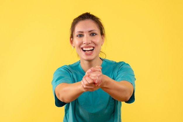 Vue de face femme médecin en chemise médicale sur fond jaune