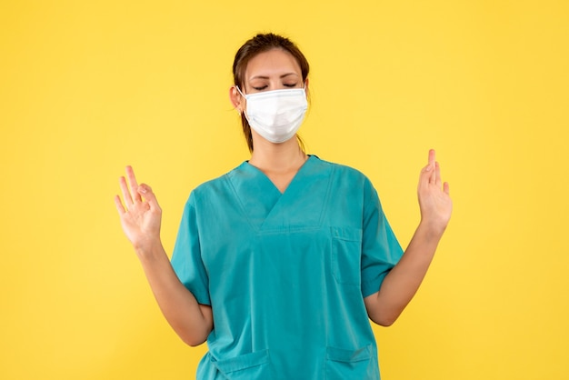 Vue de face femme médecin en chemise médicale et masque sur fond jaune