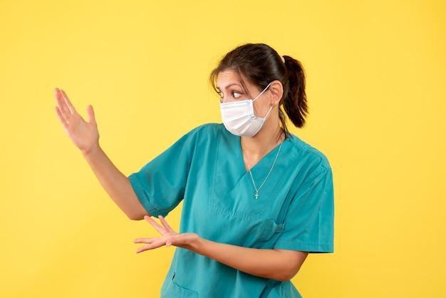 Vue de face femme médecin en chemise médicale et masque stérile sur fond jaune