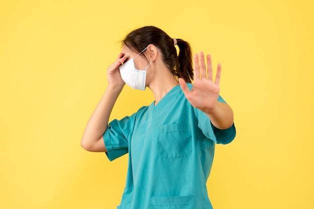 Vue de face femme médecin en chemise médicale et avec masque stérile sur fond jaune