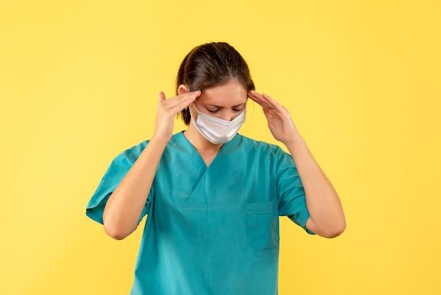 Vue de face femme médecin en chemise médicale avec masque stérile souffrant de maux de tête sur fond jaune