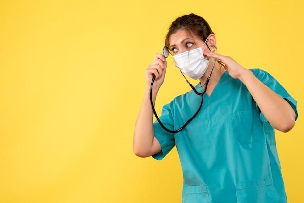 Vue de face femme médecin en chemise médicale et masque avec stéthoscope sur fond jaune
