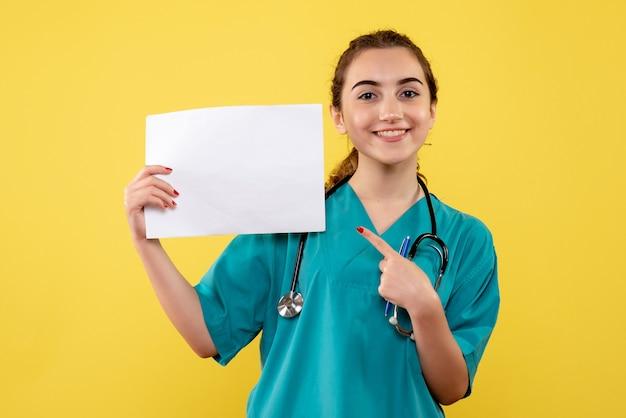 Vue de face femme médecin en chemise médicale avec papiers et stéthoscope, virus pandémique santé uniforme covid-19 émotion