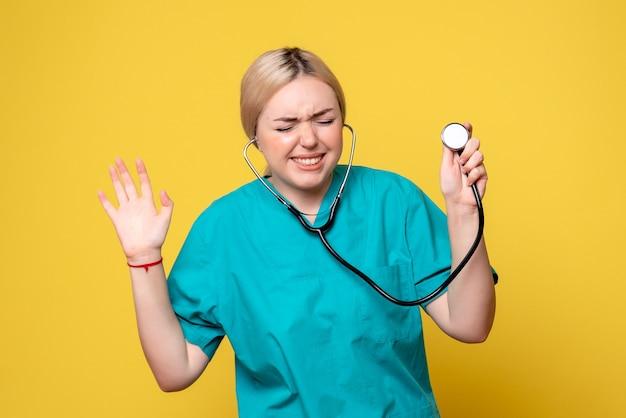 Vue de face de la femme médecin en chemise médicale avec stéthoscope sur mur jaune