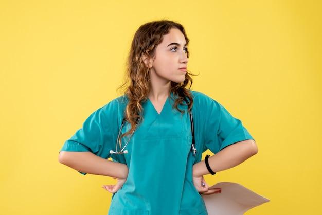 Vue de face femme médecin en chemise médicale tenant l'analyse du papier, virus de la santé pandémique uniforme covid-19 émotion