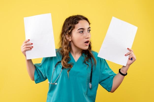 Vue de face femme médecin en chemise médicale tenant l'analyse du papier, virus uniforme des émotions de pandémie de santé covid-19