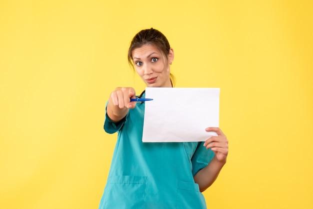 Vue de face femme médecin en chemise médicale tenant l'analyse de papier sur fond jaune