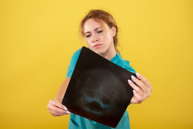 Vue de face femme médecin en chemise médicale tenant x-ray, couleur virus pandémique de l'émotion de la santé covid-19