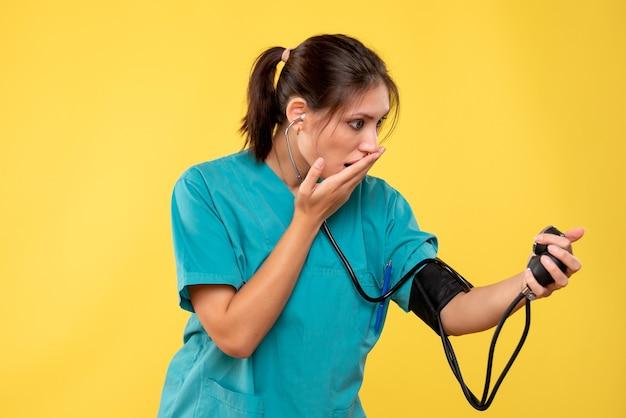 Vue de face femme médecin en chemise médicale vérifiant sa pression sur fond jaune