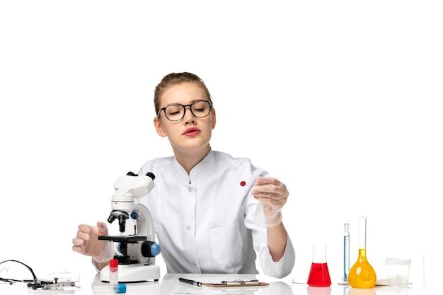 Vue de face femme médecin en combinaison médicale avec des gants en cours de travail sur un bureau blanc