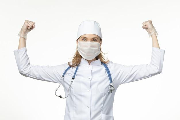 Vue de face femme médecin en combinaison médicale avec masque et gants en raison de la flexion du coronavirus sur le virus pandémique de la maladie du mur blanc clair