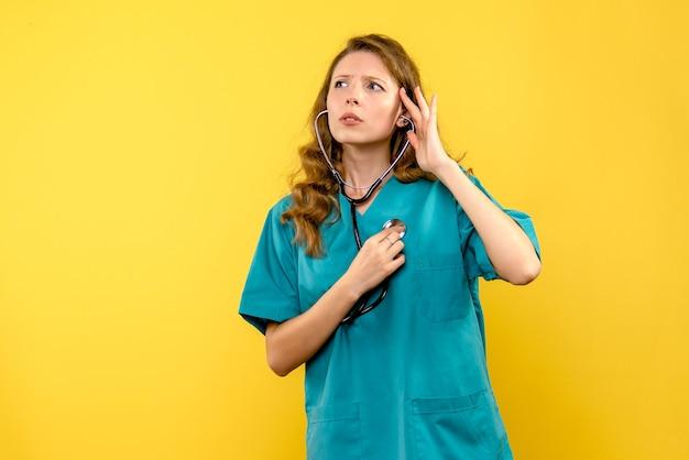 Vue de face femme médecin contrôle des battements de coeur sur l'espace jaune